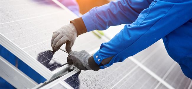 Trabajador reparando un panel solar