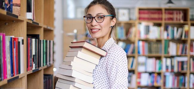 Mujer sosteniendo una pila de libros